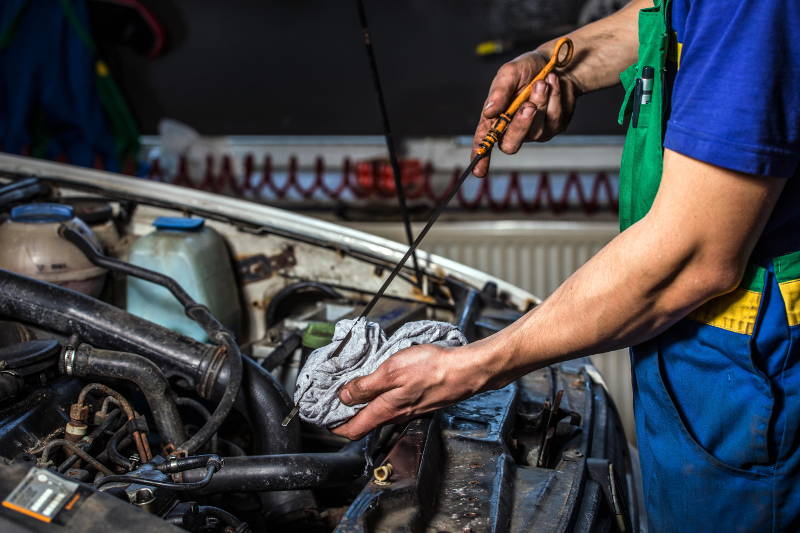 checking the engine oil level during an oil change