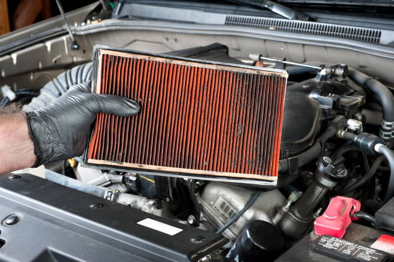 mechanic pulling a dirty air filter out of a car during a tune up