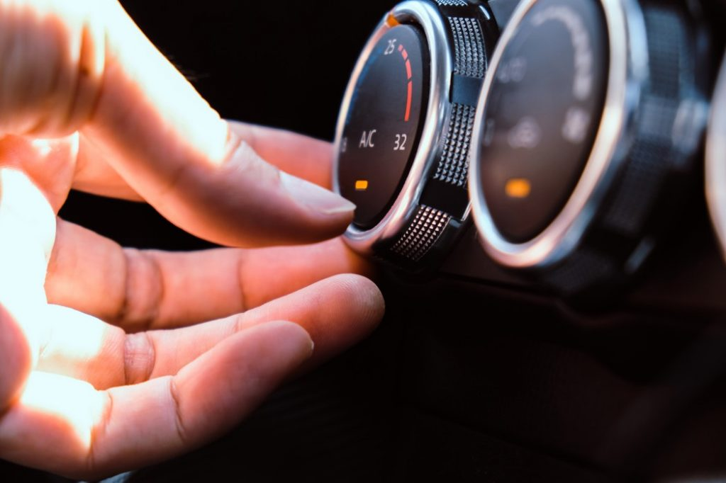 woman adjusting the car ac